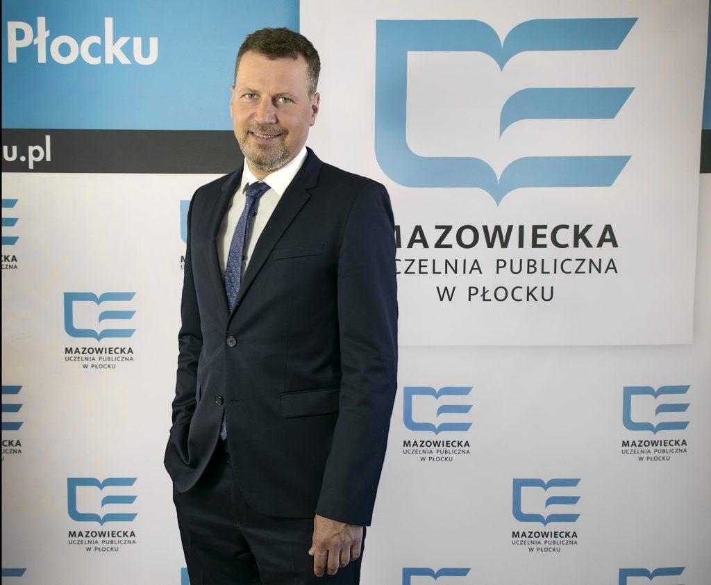 Zdjęcie przedstawiające Rektora na tle Logo Uczelni